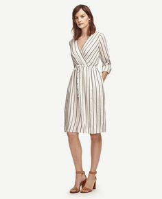 """Sporting a drawstring waist and casual roll sleeves, our striped shirtdress is ready for a very stylish season. V-neck with crossover front. 3/4 rolled sleeves with button tabs. Tunneled drawstring waist ties with elasticized back. Shirred front and back waist. h button tabs. Button front. Self tie belt. Button cuffs. Back yoke with box pleat. Shirttail hem. 21"""" from natural waist."""