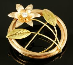 """$125.  July 2013.  14K Rose gold and yellow gold circular pin with diamond and flower, approximately 1 3/4""""dia, 0.3 oz / 5 dwt tw."""