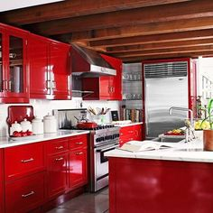 I LOVE RED. This kitchen is crazy-fun. I love how the beams, subway tile, and marble counters seem to add coziness to the modern palette of red, white, and stainless. Would you be so bold with cabinets?!