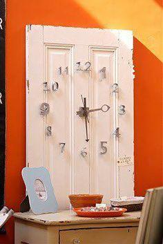 Un reloj con un vieja puerta o postigo.