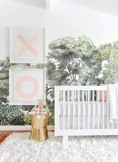 Feminine nursery with bold wallpaper, a white crib, and a white rug