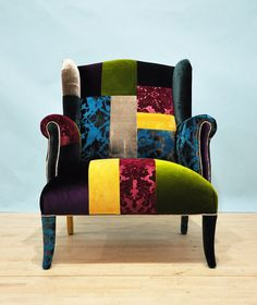 A handmade unique wingback armchair upholstered with velvet fabrics in patchwork style. Beautiful combination of lovely colors. Beech wood