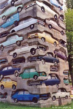 """ARMAN  """"Long Term Parking"""", 1982, Dimensions: 1950 cm, Description : Accumulation of 60 automobiles in concrete. 19,5 m. Parc de sculpture Le Montcel, Jouy-en-Josas, France"""