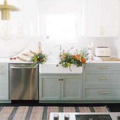The classic beauty of the farmhouse-style single-basin, enameled cast iron sink adds timeless elegance to the kitchen. Includes a tall apron front. Light Green Kitchen, Green Kitchen Island, Sage Kitchen, Farmhouse Sink Kitchen, Kitchen Redo, Home Decor Kitchen, Kitchen Interior, New Kitchen, Home Kitchens