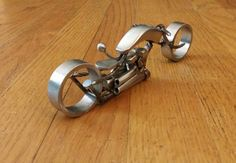 This is a scrap metal motorcycle sculpture. It measures 7 1/4 long, 2 wide and 2 1/8 tall. It is all stainless steel scrap metal with a wire