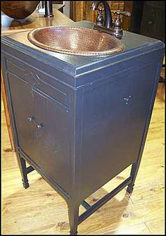 This antique Victrola cabinet was re-purposed to be a bathroom vanity. And this is about as small a bathroom cabinet as we ever make. It is small but not short, which is very important. This tiny but stately vanity has a vintage rubbed black painted finish with a hammered copper sink and a Price-Pfister bronze faucet. The copper sink gives it an extra punch of color and interest.