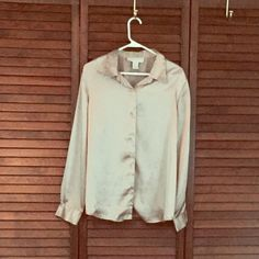 Metallic Tan/ gold button down blouse Silky button down blouse perfect for any special occasion with black pants.  Long sleeves and collar. 100% Polyester, excellent condition. Norton  Tops Blouses