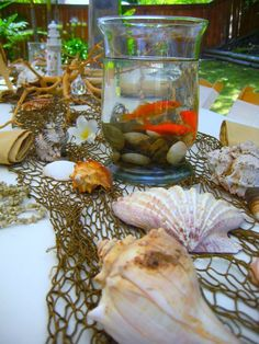 Seashell and Goldfish Table Decor. Make sure your pet fishies are not in the sun! (or use Betta fish, they like small containers, but one Betta fish per container.)