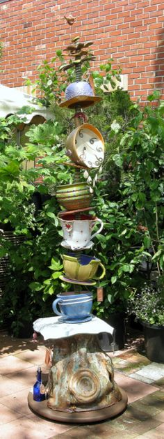garden totem of teacups and clocks...very Alice in Wonderland ish