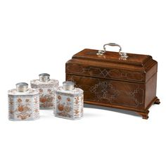 A George II mahogany and white metal inlaid tea caddy circa 1750 the interior containing three 18th century Chinese export ceramic cannisters with white metal tops,