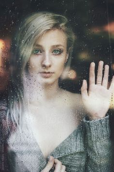 Beautiful young woman woman standing at the window watching the rain by Jovana Rikalo