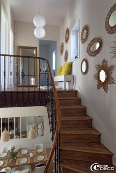 The staircase of the house of Florence Bouvier is decorated with a collection of vintage rattan sunburst mirrors