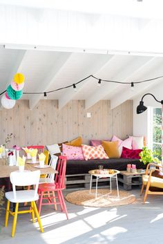 A bright and fun boho look for your garden patio. Mismatched cushions, draped lights, wooden chairs and bunting. More ideas at http://www.redonline.co.uk
