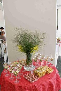 Mesa de entradinhas: cuscuz, batatinhas vinagrete, salame, patês e salada verde em taças de acrílico.