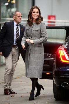 Kate Middleton kept her baby bump under wraps as she chose an elegant red shift dress and a tailored gray tweed coat for an appearance at the Children's Global Media Summit in Manchester.