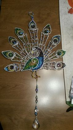 Wire wrapped beaded Peacock suncatcher with beads and crystals.