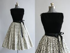 This 1950s deadstock Candy Jones party/holiday dress features a black velveteen bodice and a black and white floral satin skirt. Cinched at