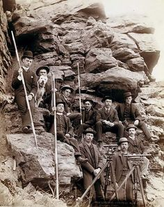 old picture of Deadwood Central Railroad Engineer Corps, showing a group of Surveyors. It was created in 1888 by Grabill, John C. H., photographer.    The photograph presents Outdoor group portrait of ten railroad engineers and a dog, posing with surveyors' transits on tripods and measuring rods, on the side of a mountain.