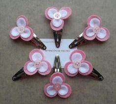 Clips o ranitas de flores de tres pétalos en rosa y blanco.