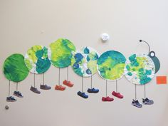 """An art project created by one of our CCLC preschool classes. The children painted large white coffee filters and the teacher photographed & printed out photos of the children's shoes. The teacher then set up the display on the classroom wall so the preschool students could admire their segment of the """"centipede."""""""