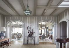 The pin-stripe design of the wall boarding alternates a white-painted beaded board with flat boards of red oak finished in a beige-gray. The two arches leading to the living and dining rooms create an open flow from the entry hall and a direct ocean view.