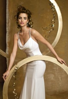 Chiffon over satin bias cut wedding dress with a drape neckline, empire waist, rhinestone cris-cross straps, and a godet bottom with a chapel length train.