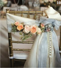 """10) DECORATED BRIDE'S CHAIR:   Gilded chevari chair bedecked with a fabric and organza sash adorned with fresh David Austin """"Juliet"""" and """"Keira"""" garden roses and Queen Anne's lace accent flowers.  The elegant sash is finished off with a pearl brooch and cascading pearls.  (Chair and linens by Apres; flowers and jewels by Haute Flower Boutique)."""