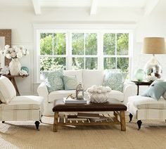 Light blue pillows, white couch, white flowers