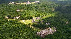 "Aerial view of Chichén Itzá showing <a href='#' class='glossary-tip' title=""Meaning ""mountain"" in Yucatec Mayan, Puuc is a region in the northwest of the Yucatán Peninsula. It is also a style of architecture characterized by skilled ornamentation."">Puuc</a>-style buildings in the foreground, the Observatory in the middle, and the Temple of <a href='#' class='glossary-tip' title=""The feathered serpent of Maya mythology."">Kukulkán</a> in the background. The Great Ball Court stands to the left…"