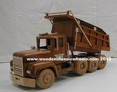 "Dump Truck   # 1988 M  three-axle dump truck with a  bed that dumps just like the big trucks.  Built from: solid cherry and black walnut w / solid hard maple wheels  have your logos put on the rubber mud flaps,doors  Approx. size 18"" Long X 10"" Tall X 8"" Wide"