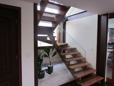 Projeto Ana Donadio - Escada em madeira vazada com guarda-corpo de vidro. Estrutura metálica na cor marrom para reforçar a estrutura da casa. Parede com textura da terracor