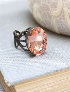 This is an old Hollywood inspired big peach glass jewel ring! The vintage style oval jewel is set in antique patina brass settings. The