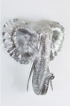 """Here we have a very stylish and modern silver Elephant head. This head simply hooks onto a screw on the wall and is a very fascinating and interesting piece of wall art, This ornament is wonderfully manufactured and will look great in any modern home. This Elephant head measures as follows 17"""" (Height) 15"""" (Width) 9"""" (Depth)."""