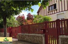 Portail Bastide coulissant motorisé, ajouré et contemporain, de coloris Rouge Pourpre qui s'harmonise parfaitement avec la façade de cette maison.