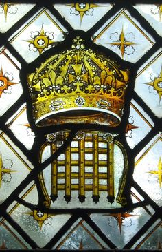 16th century armorial badge (a crown surmounting a portcullis) set in 19th century quarry glazing in the south aisle at St Peter's Church at Elford, Staffordshire, England