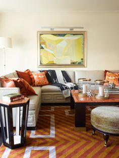 A corner suite designed by BAMO at The New York Palace Hotel features a comfortable sectional sofa with nailhead detail. The Greek key pattern of the sofa trim is echoed in the design of the rug, while the warm chevron pattern and rust-colored accents provide contrast and warmth to the space.