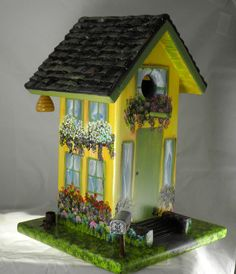 Unique, gorgeous birdhouse handcrafted and hand painted yellow and green with a lot of flowers and a car in the garage. This birdhouse was built out of pine; the roof is carved to look as if it has individual shingles on it. We, then, seal the birdhouse with a clear coat and then prime it with a white primer, after which, I get to paint it any way I want. I could see that this birdhouse needed lots and lots of flowers. It also has a beehive and a swing hanging off the eaves, and last but not…