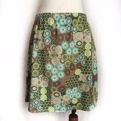 "Athleta Green Floral A-Line Skirt Lightweight, pull-on style skirt in a fun floral pattern with green, blue, brown and yellow. Thin and stretchy with an elastic waistband. Can be worn alone or sported over your bikini bottoms as it is water friendly. 85% polyester; 15% elastane. Machine wash. Size Medium. Waist: 15"" flat across, unstretched and approx. 16.5"" stretched.  Hip: 21"" across, unstretched.  Length: 20"". Like New Condition. Thanks for looking! Athleta Skirts A-Line or Full"