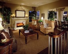 This living room features twin golden rolled arm chairs facing brown floral sofa over a lush, dark wood coffee table. White framed fireplace, dark hardwood flooring, and greenery throughout complete the look.