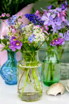 Floral Arrangement Vignette ~ mixed flowers in colored vases and bottles...