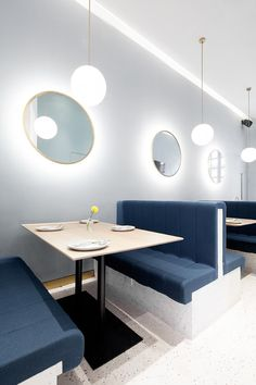 This modern restaurant booth seating with blue upholstery and round backlit mirrors on the wall. #ModernRestaurant #BoothSeating