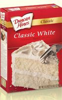 Duncan Hines Classic White Cake Mix - follow instructions on box and add 2 tbsp of all purpose flour, 1 tbsp sugar, 1 tsp vanilla to mix. Cake comes out a bit more dense yet moist. By far the best buy box mix w/ add-ins I've tried.