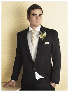 Black suite, with ivory vest and gold tie.