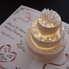 such a wonderful idea for a wedding card! here is a template for making a cake kinda like this one (you will have to add the bow, flowers, and light) http://manaelf.com/projects/centerpost.pdf