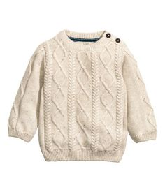 Cable-knit sweater in a soft cotton blend with wool content. Buttons on one shoulder and long sleeves.