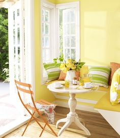 The owners of this California bungalow chose Sherwin-Williams's Convivial Yellow for their breakfast nook, furnished with a built-in bench and a scalloped-top pedestal table from Ethan Allen.