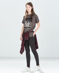 grey printed t-shirt with plaid wrapped around and jeans