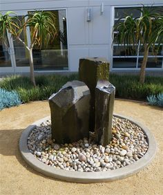 I love this basalt water feature surrounded by large stones, a concrete circular border and decomposed granite. This is at SoCo Design center in Costa Mesa, CA. The grass in the background is Dianella, with Senecio, and tree aloes as the vertical element.