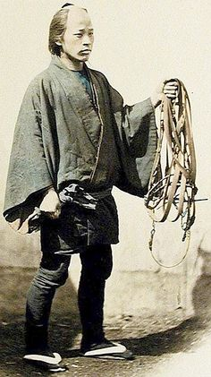 The horse groom of a samurai carrying tack.
