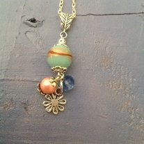 This is a beautiful hand made necklace with a large pink and white bead. There is a big silver swirl hanging from the pink bead. It is very pretty and unique. The Silver swirl is dangling from the bottom of the  beads.  looks great when you are wearing it!- these charms are also available for sal...